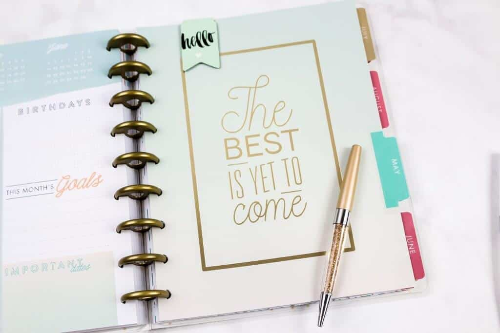 Hello the best is yet to come quote in a journal with a gold pen.