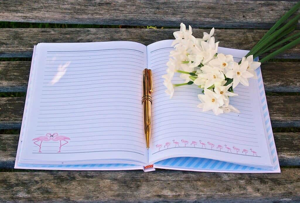 A bullet journal with flowers and a gold pen on a wooden table.
