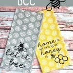 Two tea towels with honey bee quotes on a painted wood background.