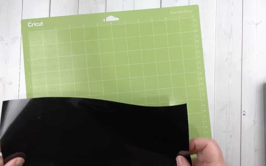 Black vinyl on a green Cricut cutting mat.