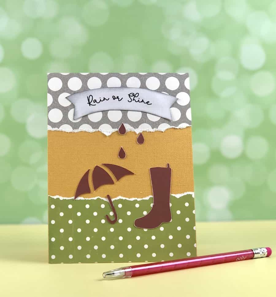 Make a greeting card sample with rain boot and umbrella.