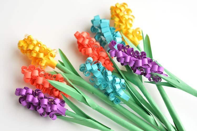 Paper hyacinth flowers with green stems.
