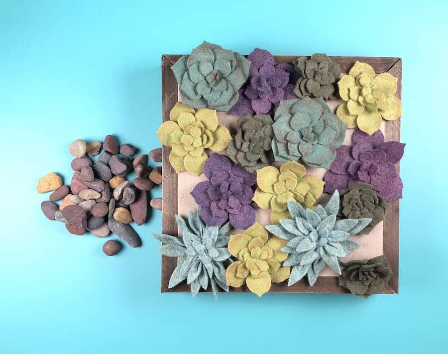 Felt succulent wall art with pebbles.
