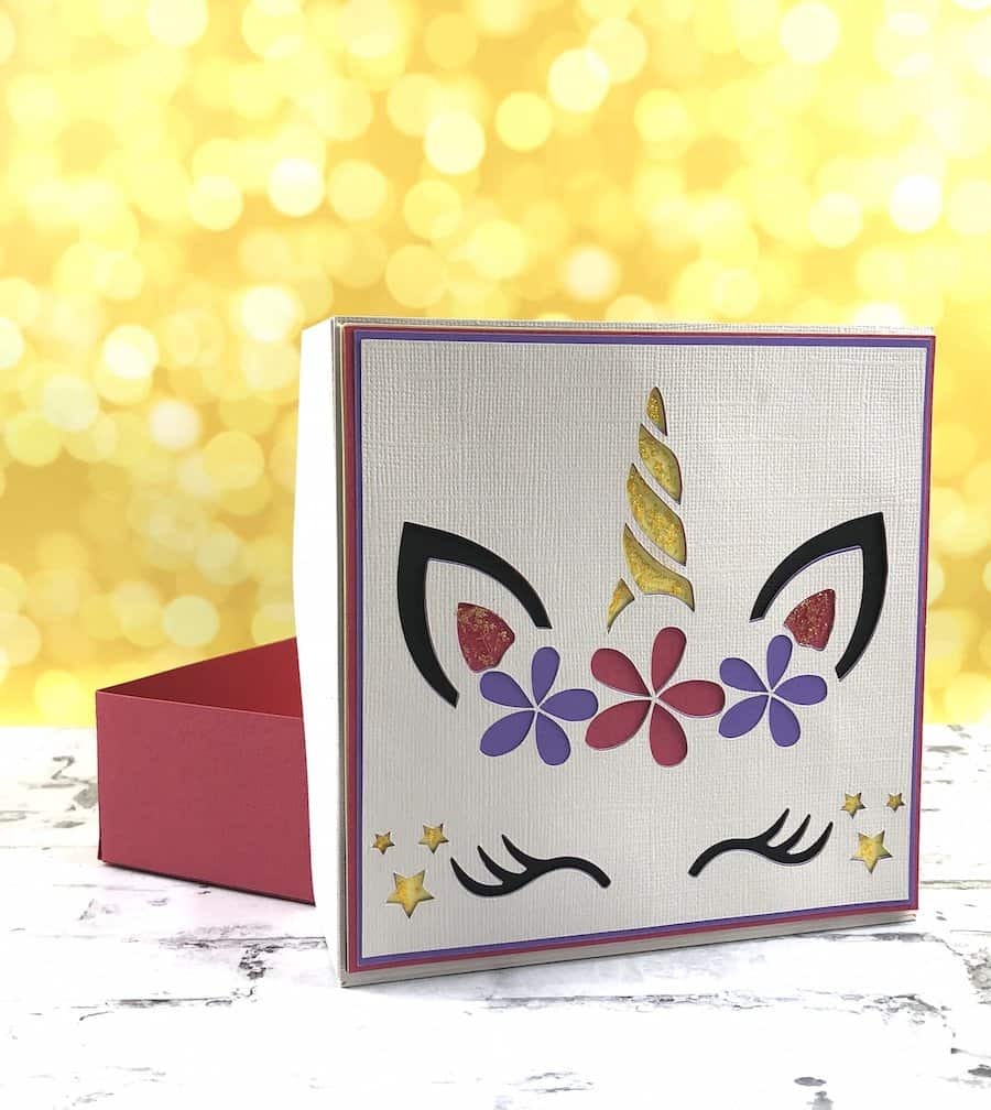Open view of a colorful unicorn paper box on a white brick background.
