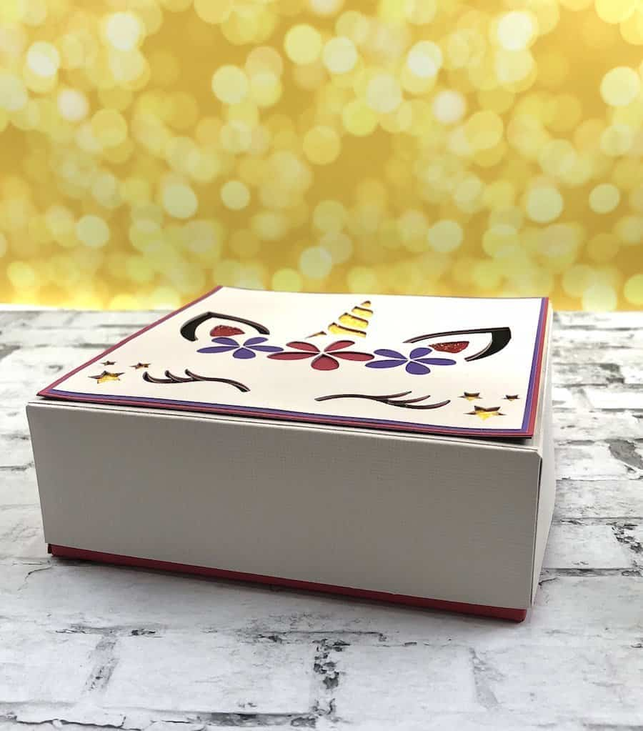 Side view of a colorful unicorn paper box on a white brick background.