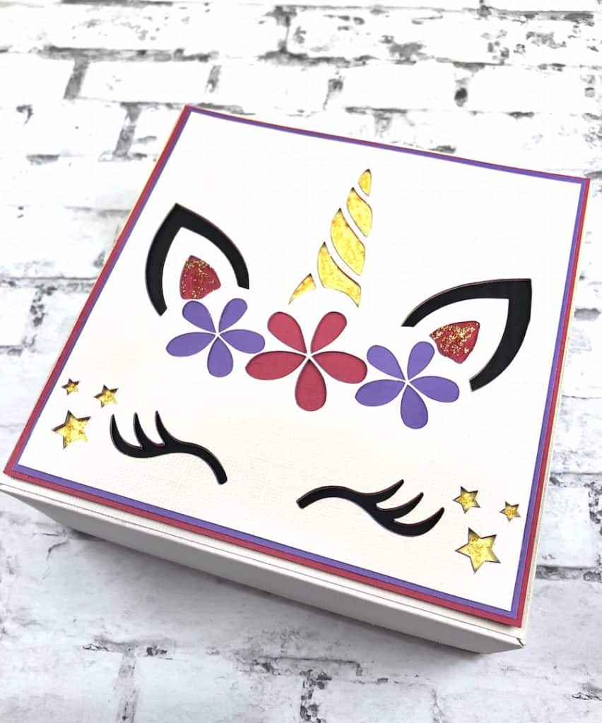 Colorful unicorn paper box on a white brick background.