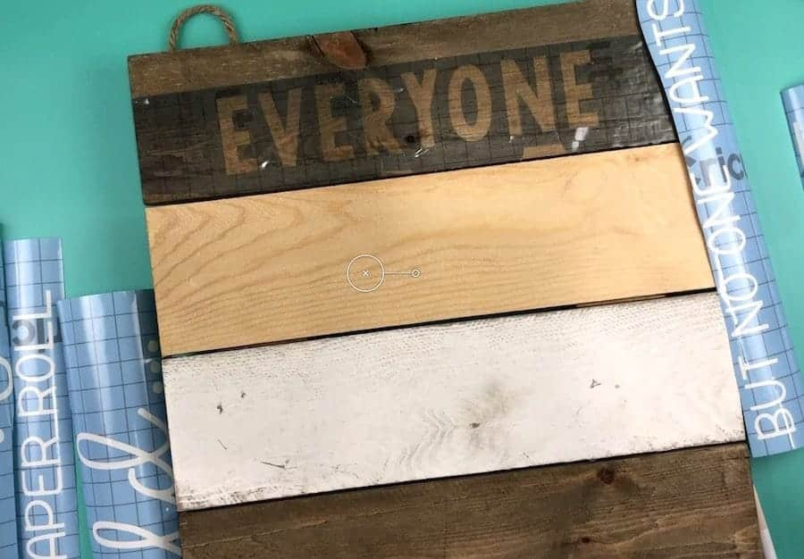 Wooden sign with stencil vinyl cut into strips.