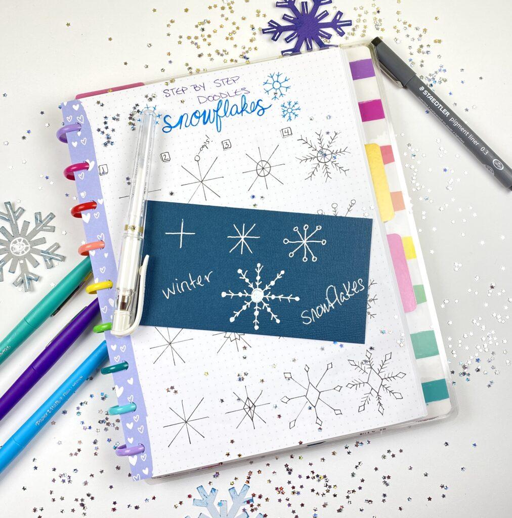 white gel pen snowflakes on darker cardstock paper