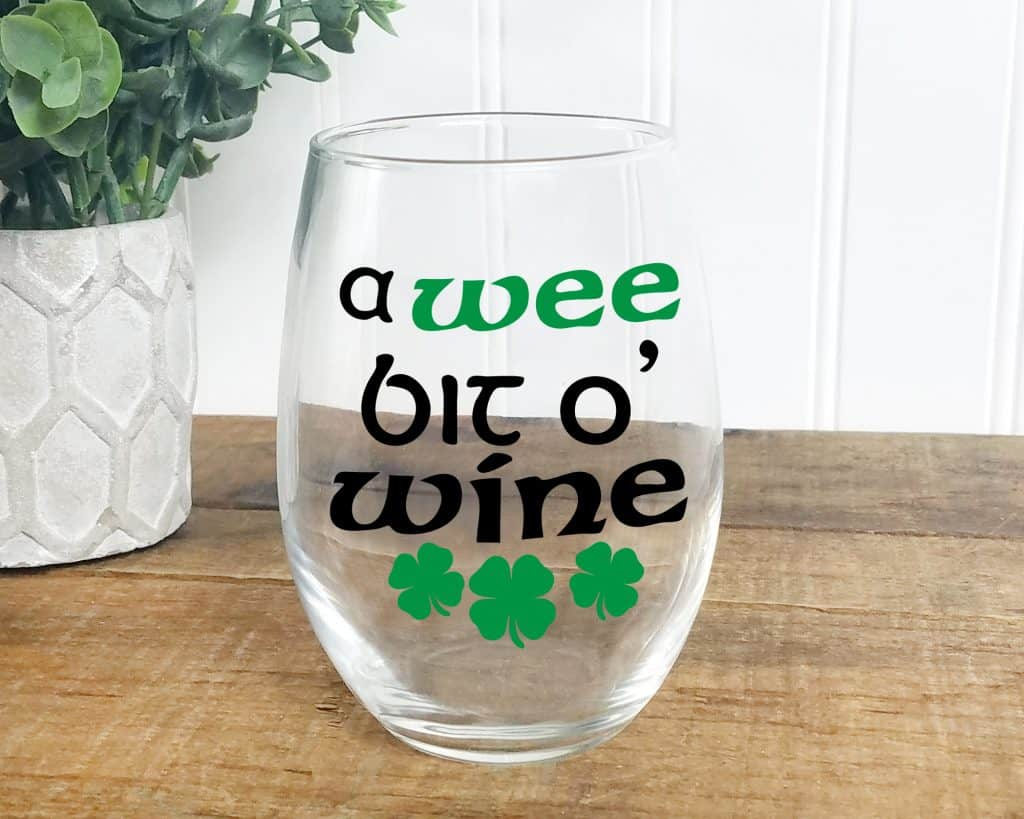 "Get this free wine glass decal for your St. Patrick's Day celebration. Craft a vinyl decal that says ""A Wee Bit O' Wine"" and enjoy the holiday. This free wine SVG file is great for Cricut and Silhouette machines."